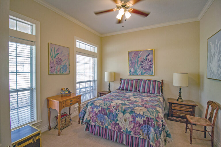 Bedroom with purple bedspread and wooden decor