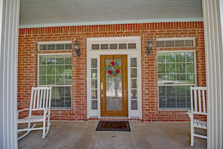 Front door with brick surrounding and rocking chairs