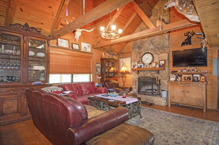 Living room with red couch and stone fireplace