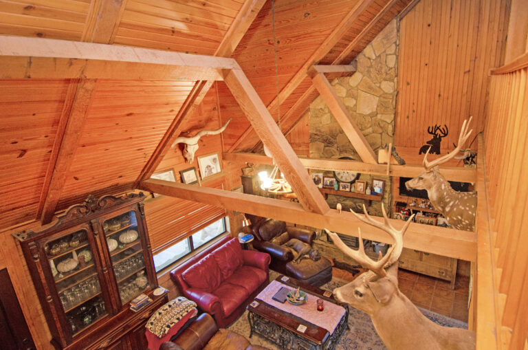View from upstairs through wooden beams to see downstairs