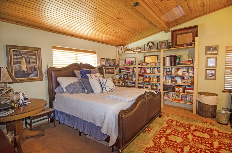 Master bedroom with large bed and bookshelves