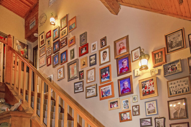 Main wood stairway with photos lining wall