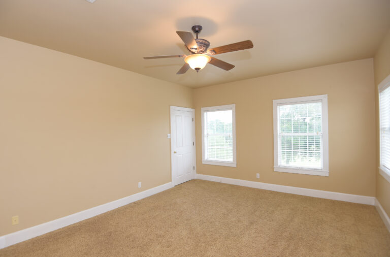 Bedroom 1 with beige carpet and three windows