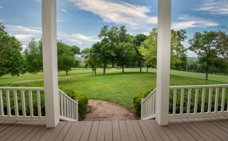 Front porch view with blue sky and green grass